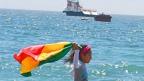 Niña portando la bandera en la costa